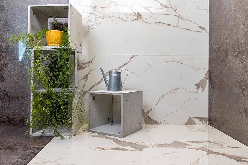 kostki betonowe z rośliną i konewką na tle płytek kamiennych