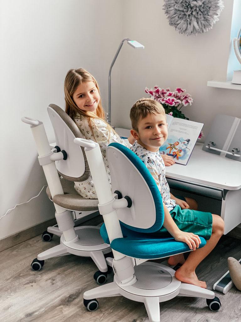 chłopiec i dziewczynka siedzące na krzesłach przy biurku