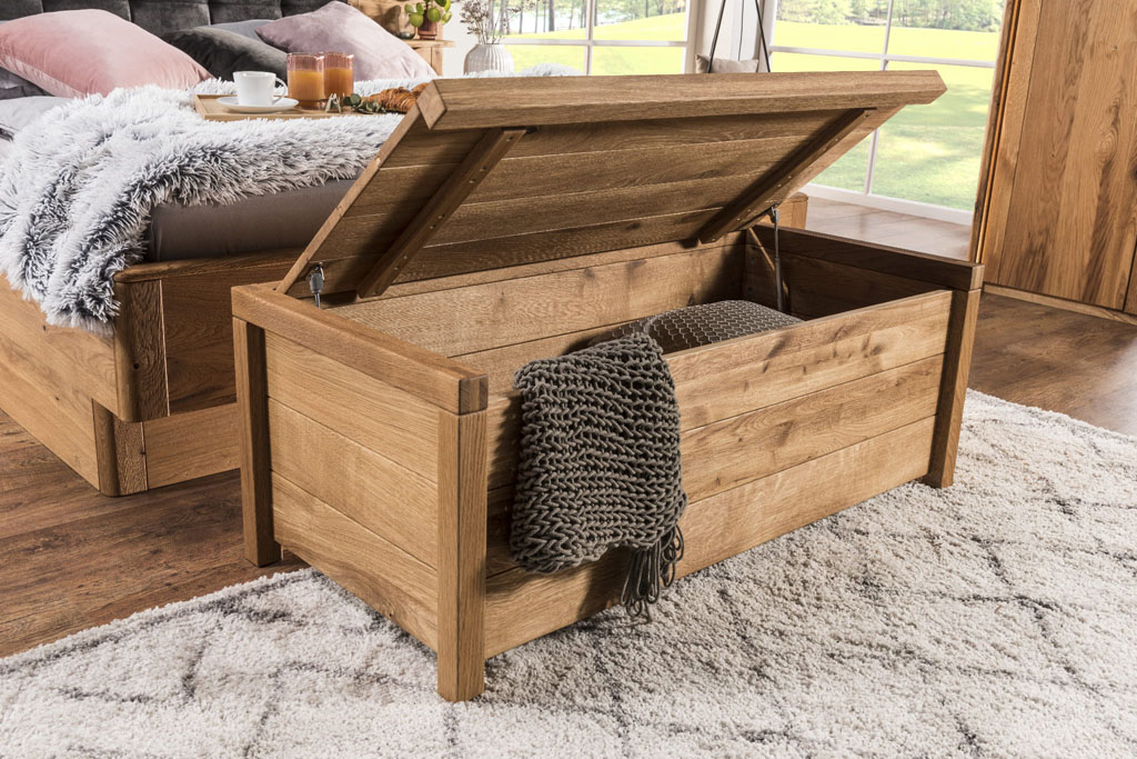 drewniana skrzynia z kocem w środku ustawiona przy łóżku