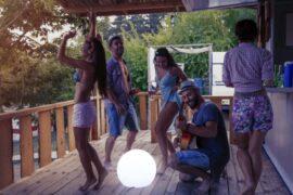 impreza na tarasie z kulistą lampą ogrodową buly