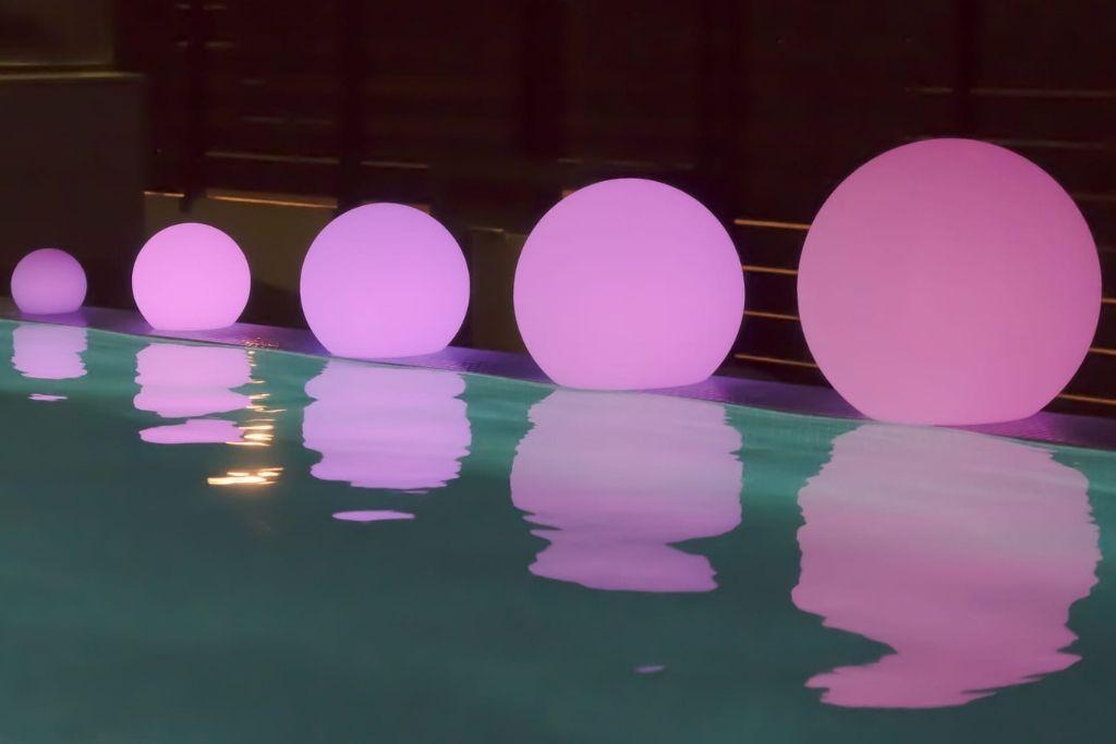 kuliste pływające lampy ogrodowe w basenie świecące na różowo