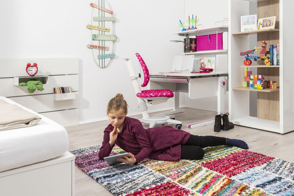 dziewczynka leży na dywanie koło biurka