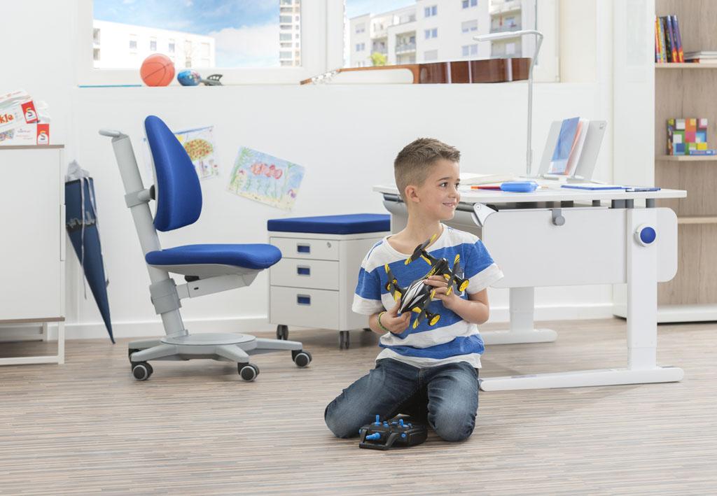 chłopiec bawiący się zdalnie sterowanym autem przy biurku