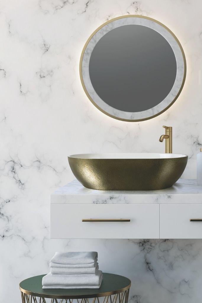 złota umywalka nablatowa w marmurkowej łazience