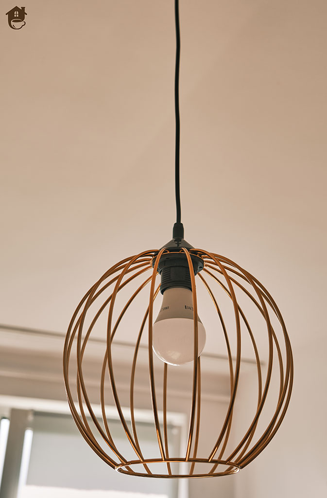 lampa miedziana kula zawieszona na suficie w salonie