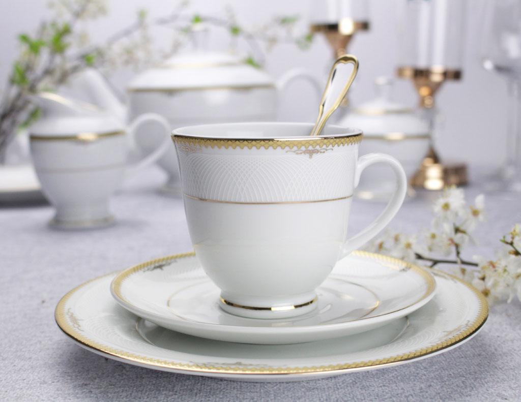 porcelanowa filiżanka i talerzyki ze złotym wykończeniem stojące na stole