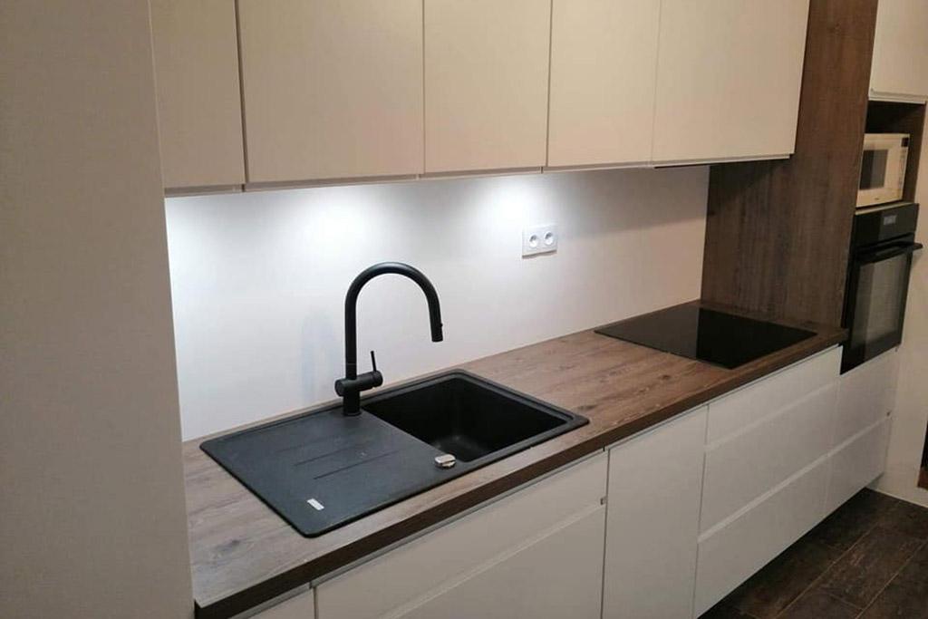 biała kuchnia z drewnianymi blatami i czarnymi elementami